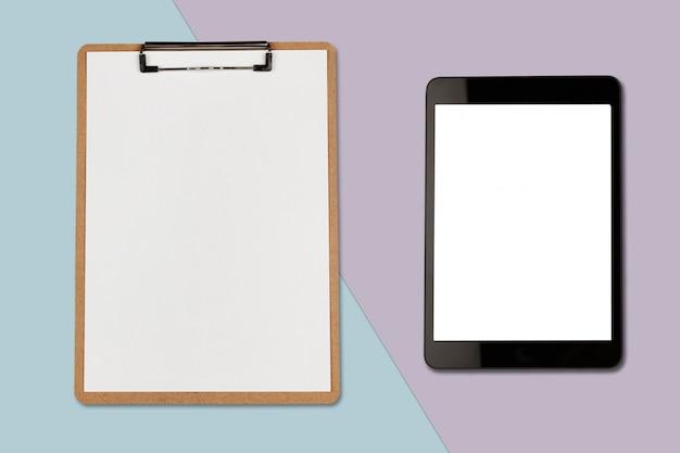 Tablette numérique avec écran vide et presse-papiers sur fond de couleur pastel, photo à plat Photo Premium