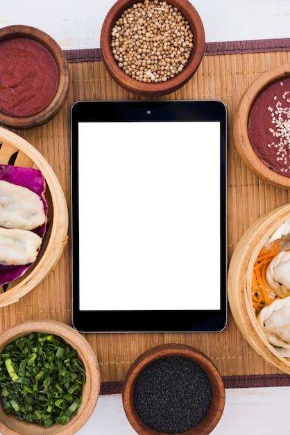 Tablette numérique entourée de bateaux à vapeur; oignon de printemps; graines de sésame et graines de coriandre sur napperon Photo gratuit