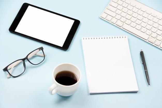 Tablette numérique; lunettes; tasse à café; bloc-notes en spirale vierge; stylo et clavier sur fond bleu Photo gratuit