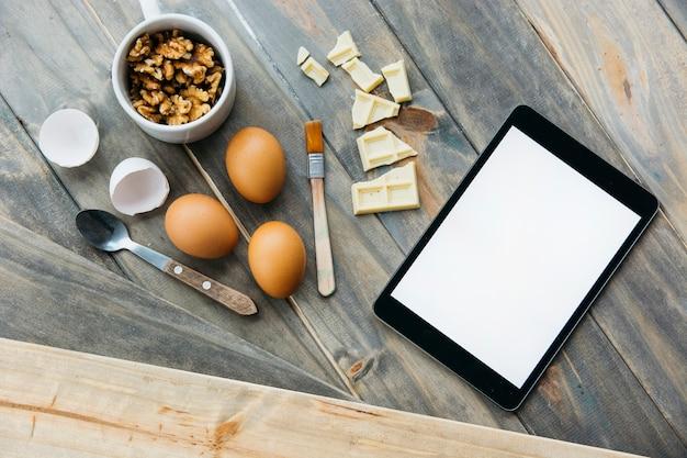 Tablette numérique près de morceaux de chocolat; oeufs et noix sur fond en bois Photo gratuit