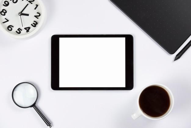 Tablette numérique avec réveil; loupe; tasse à café et tablette numérique graphique avec stylet sur fond blanc Photo gratuit