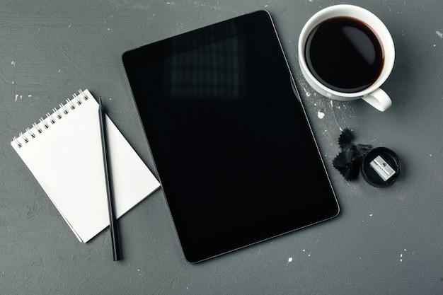 Tablette numérique et tasse de café sur le bureau en bois. Photo Premium