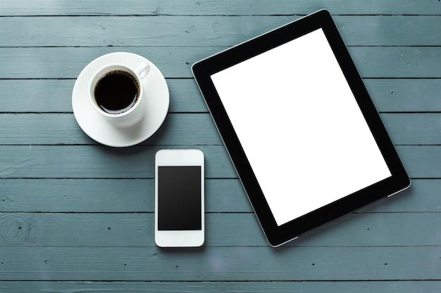 Tablette numérique et tasse à café sur une table en bois Photo Premium