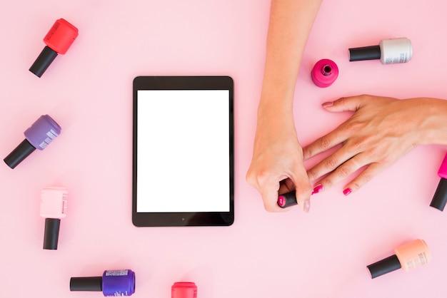 Tablette vue de dessus entourée de vernis à ongles Photo gratuit