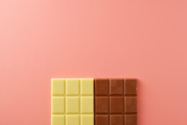 Tablettes de chocolat blanc et noir sur rose Photo Premium