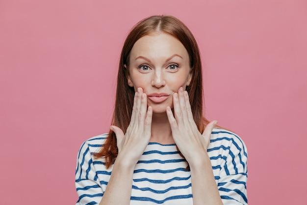 Tache de rousseur jolie femme garde les mains près des lèvres, a un maquillage minimal, une peau saine Photo Premium