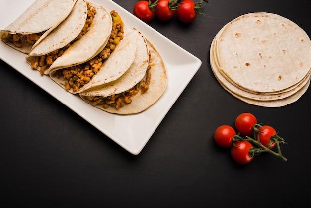 Taco sur assiette près de tomates Photo gratuit