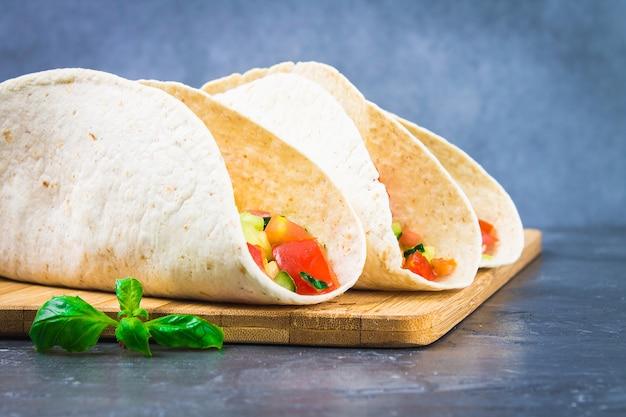 Tacos mexicains traditionnels avec viande et légumes sur fond en bois Photo Premium