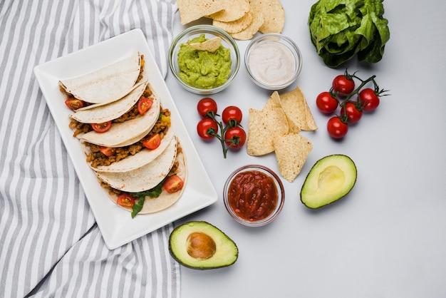 Tacos sur plat dans la serviette près des légumes et des sauces Photo gratuit