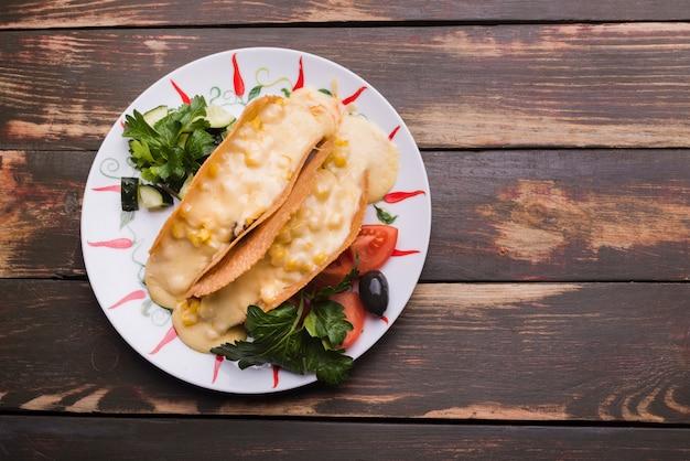 Tacos à la sauce parmi les légumes sur le plat Photo gratuit