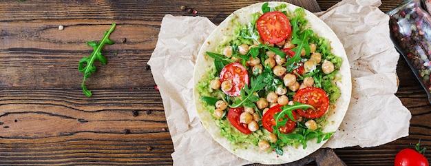 Tacos Végétaliens Au Guacamole, Pois Chiches, Tomates Et Roquette. Nourriture Saine. Petit Déjeuner Utile. Mise à Plat. Vue De Dessus Photo Premium