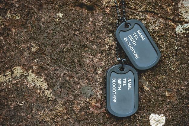 Tag Militaire Pendu Sur Le Rocher Sur Le Fond De Roche Dans La Forêt. Concept De Sacrifice De Soldat Et D'armistice. Photo Premium