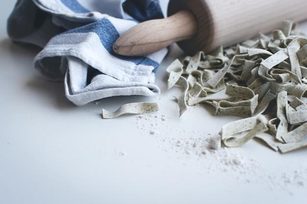 Tagliatelle de pâtes recouverte de farine avec un rouleau en bois sur fond blanc Photo gratuit