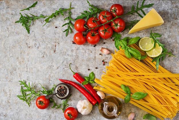 Tagliatelles De Pâtes Et Ingrédients Pour La Cuisson (tomates, Ail, Basilic, Piment). Vue De Dessus Photo gratuit