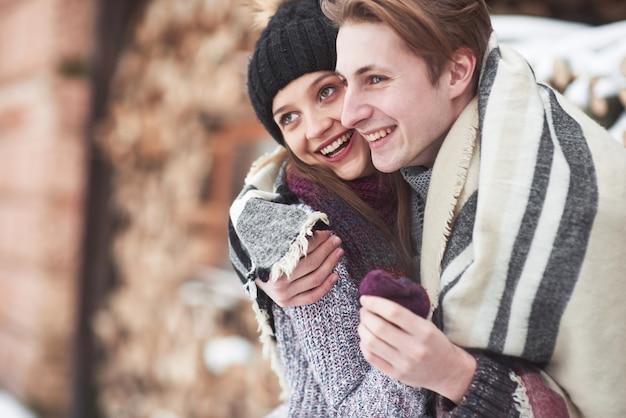 Taille portrait d'insouciant jeune homme et femme embrassant et souriant. ils sont debout dans la forêt d'hiver et regardant la caméra avec bonheur Photo Premium