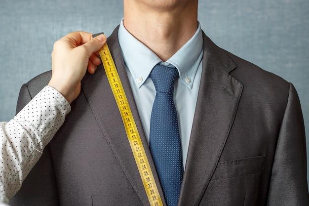 Le tailleur mesure le costume avec un gros plan de ruban à mesurer Photo Premium