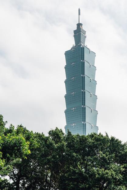 Taipei 101 bâtiment avec des branches d'arbres ci-dessous avec un ciel bleu et nuage à taipei, taiwan. Photo Premium