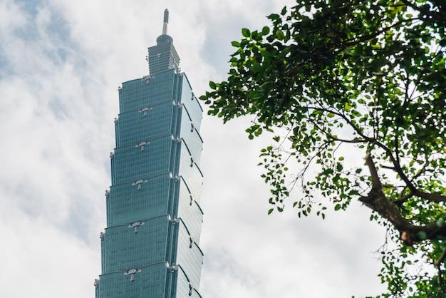 Taipei 101 bâtiment avec des branches d'arbres sur le côté droit avec ciel bleu et nuages à taipei, taiwan. Photo Premium