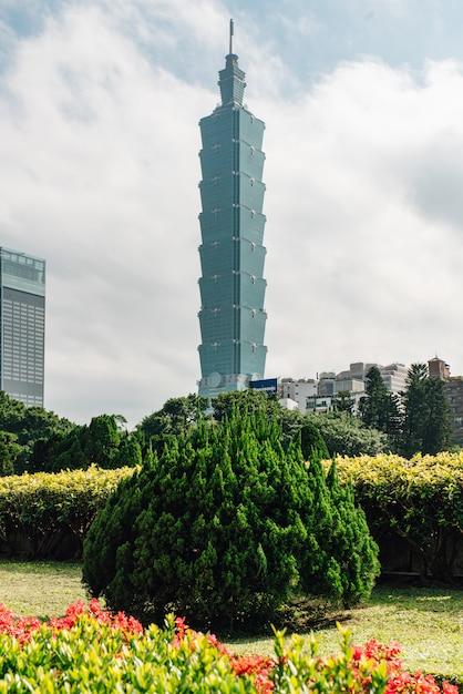 Taipei 101 bâtiment avec des buissons d'arbres au premier plan. Photo Premium
