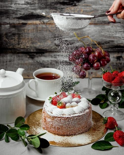 Tamis En Poudre De Femme Sur Le Gâteau Aux Fruits Photo gratuit
