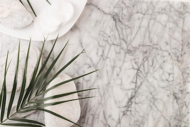 Tampons de coton circulaires; pierres de spa et feuille de palmier sur fond texturé en marbre Photo gratuit