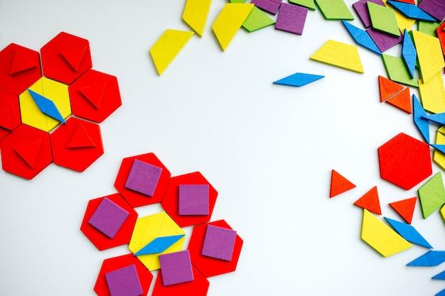Tangram en bois de couleur en forme de fleur sur fond blanc Photo Premium