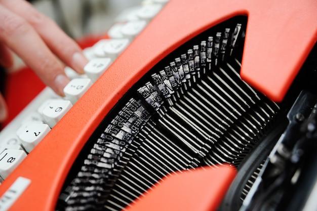 Taper sur une machine à écrire vintage. mains de fille en tapant sur un clavier de la vieille machine à écrire Photo Premium