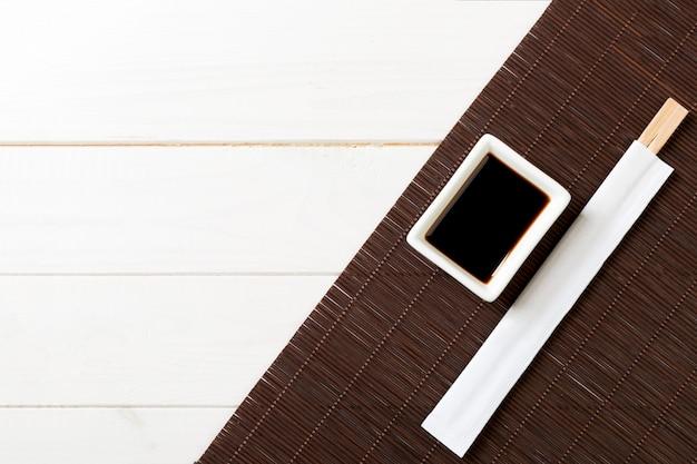 Tapis de bambou et sauce soja avec des baguettes de sushi sur une table en bois blanche Photo Premium