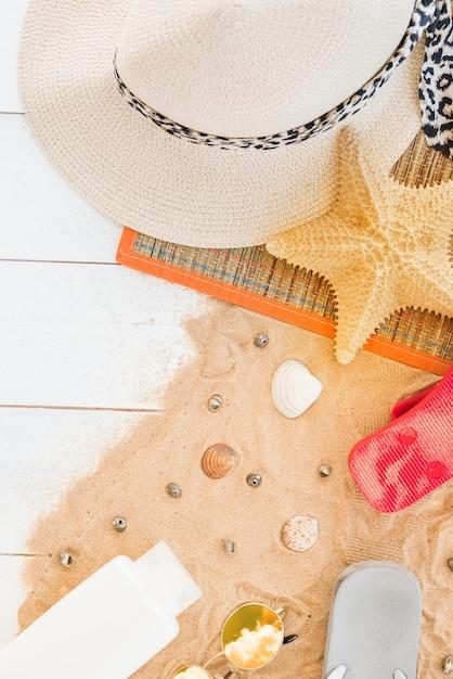 Tapis avec chapeau et étoile de mer près de coquillages et bouteille sur le sable Photo gratuit