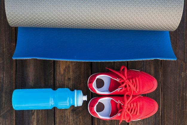 Tapis d'exercice enroulé avec une bouteille d'eau et une paire de chaussures de sport sur une table en bois Photo gratuit