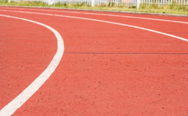 Tapis roulant rouge courbe au stade et ligne blanche sur fond flou Photo Premium
