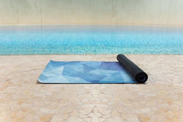 Tapis de yoga bleu à l'intérieur de la salle de sport après un cours de yoga à l'étage près d'une piscine, gros plan Photo Premium