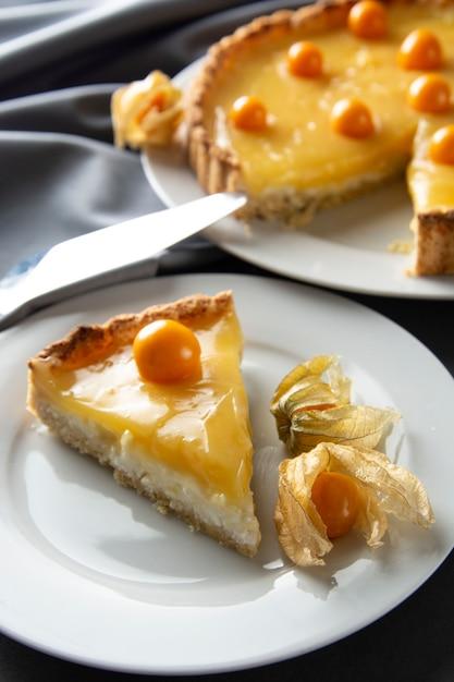 Tarte au citron et à la tarte, tarte délicieuse faite maison. dessert sucré. tarte au citron et au curd décorée de physalis. Photo Premium