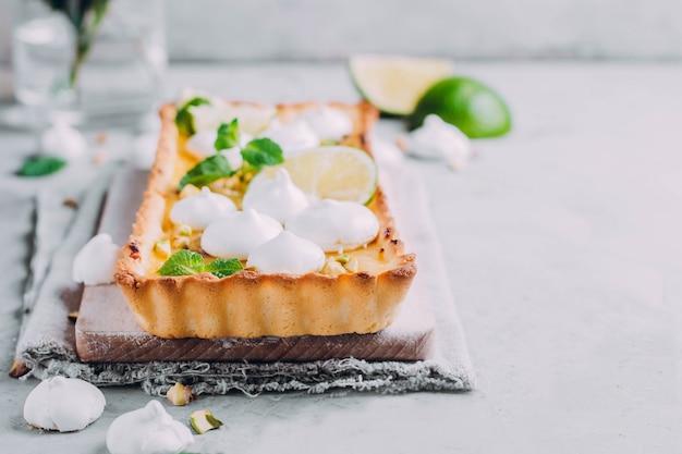 Tarte au citron vert et au citron, aux pistaches de noix et à la meringue. gateau aux agrumes Photo Premium
