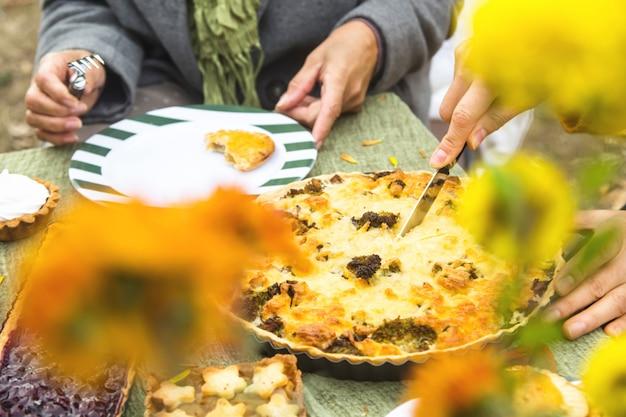 Tarte Au Fromage Copieuse Maison Sur La Table. Femme Coupe Une Tarte Pour La Famille. Photo Premium