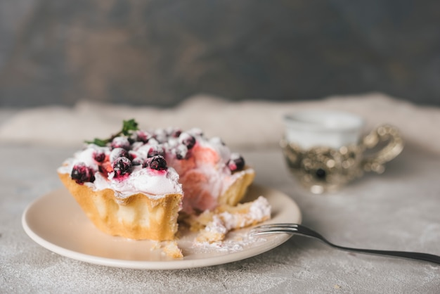 Tarte aux fruits mangés sur une assiette en céramique avec une fourchette en acier inoxydable Photo gratuit