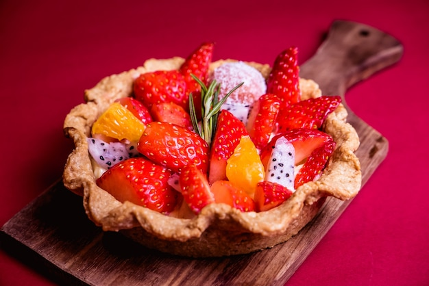 Tarte aux fruits mélangés frais sur fond rouge Photo Premium