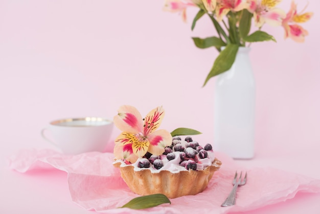 Tarte aux myrtilles décorée de fleur d'alstroemeria sur fond rose Photo gratuit