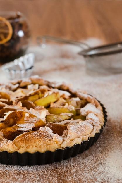 Tarte aux pommes dans un moule avec du sucre en poudre Photo gratuit