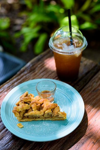 Tarte aux pommes avec du café sur une table en bois dans le jardin Photo Premium