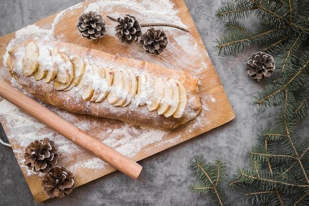 Tarte aux pommes sur une planche en bois avec des cônes Photo gratuit
