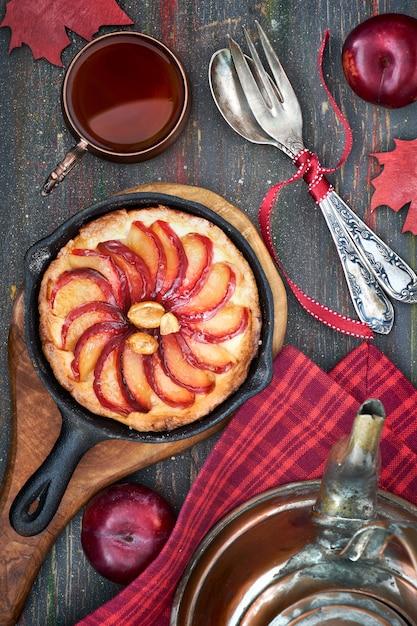 Tarte aux prunes maison cuite au four dans une poêle en fonte servie avec des cacahuètes sur planche de bois Photo Premium