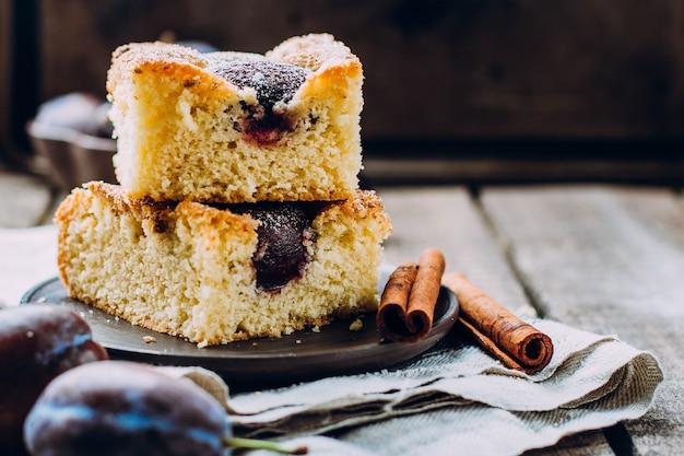 Tarte maison aux prunes sur le fond de la table en bois. gâteau d'automne aux fruits à la cannelle. Photo Premium