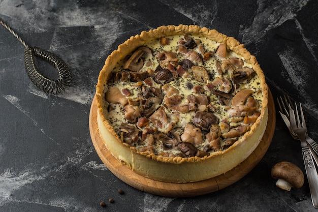 Tarte quiche aux champignons avec champignons et fromage sur fond sombre Photo Premium