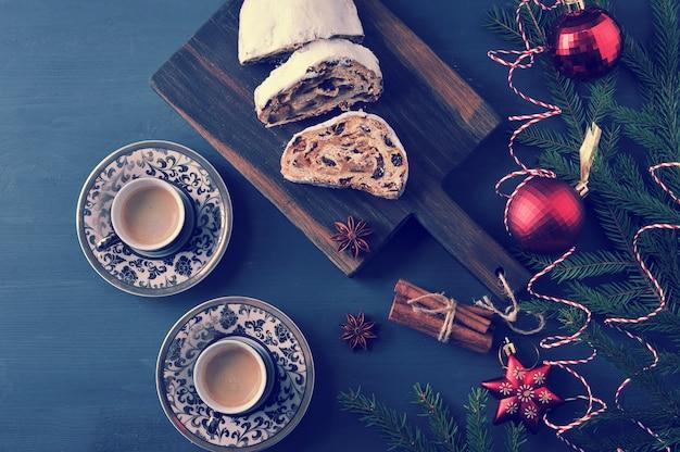 Tarte traditionnelle de noël avec des raisins secs et des noix avec des branches d'arbres et des jouets, et deux tasses de café Photo Premium