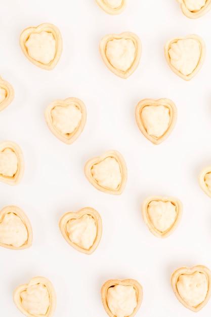 Tartelette en forme de coeur remplie de crème fraîche isolée sur fond blanc Photo gratuit