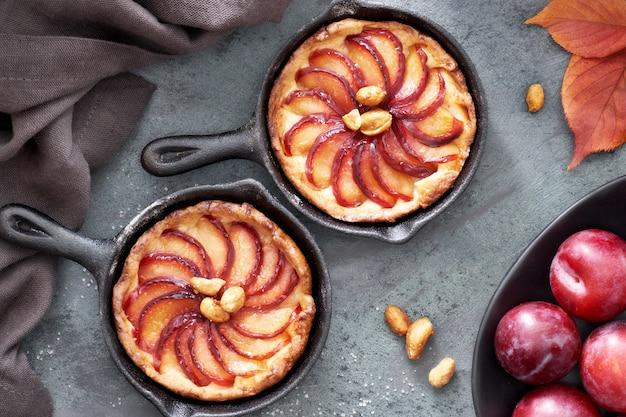 Tartelettes de crumble faites maison avec des tranches de prune cuites dans de petites poêles en fer Photo Premium