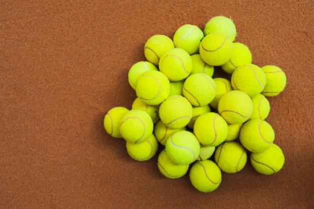 Tas de balles de tennis vertes sur un court de tennis Photo gratuit