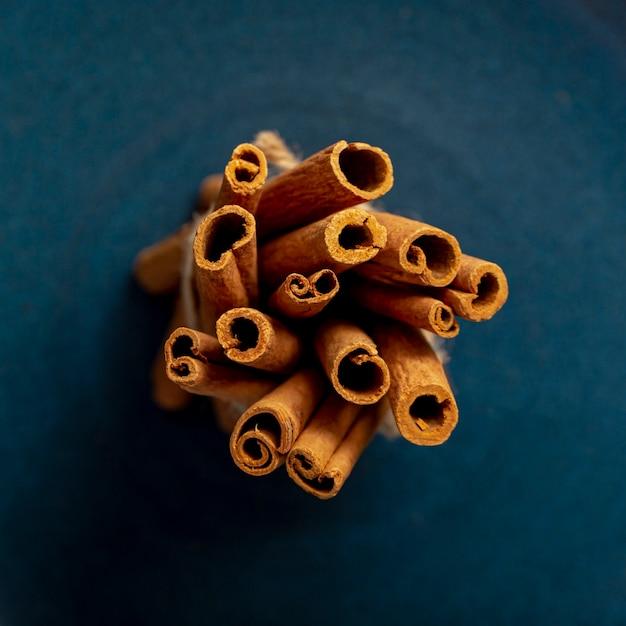 Tas de bâtons de cannelle sur un fond bleu foncé Photo gratuit