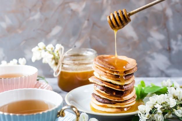 Un tas de beignets à côté d'une tasse de thé et un pot de miel sur un fond gris Photo Premium